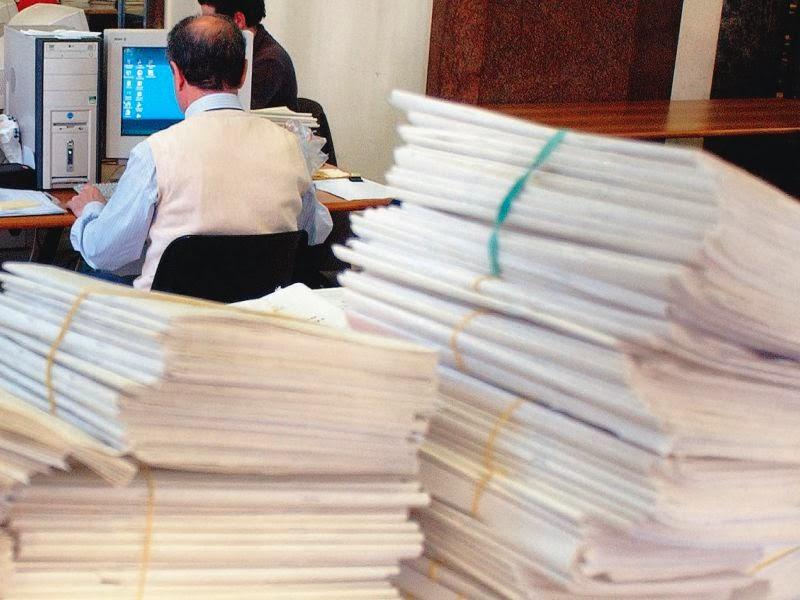 Un impiegato sommerso da documenti