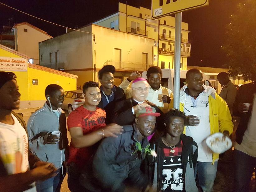 Mons. Bertolone, con un gruppo di giovani immigrati durante la consegna dei pasti serali