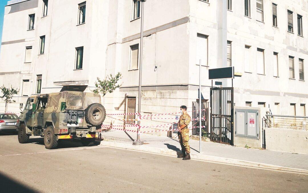 L'esercito che presidia l'ingresso del centro di accoglienza nell'ex Ferrhotel vicino alla stazione inferiore di Potenza