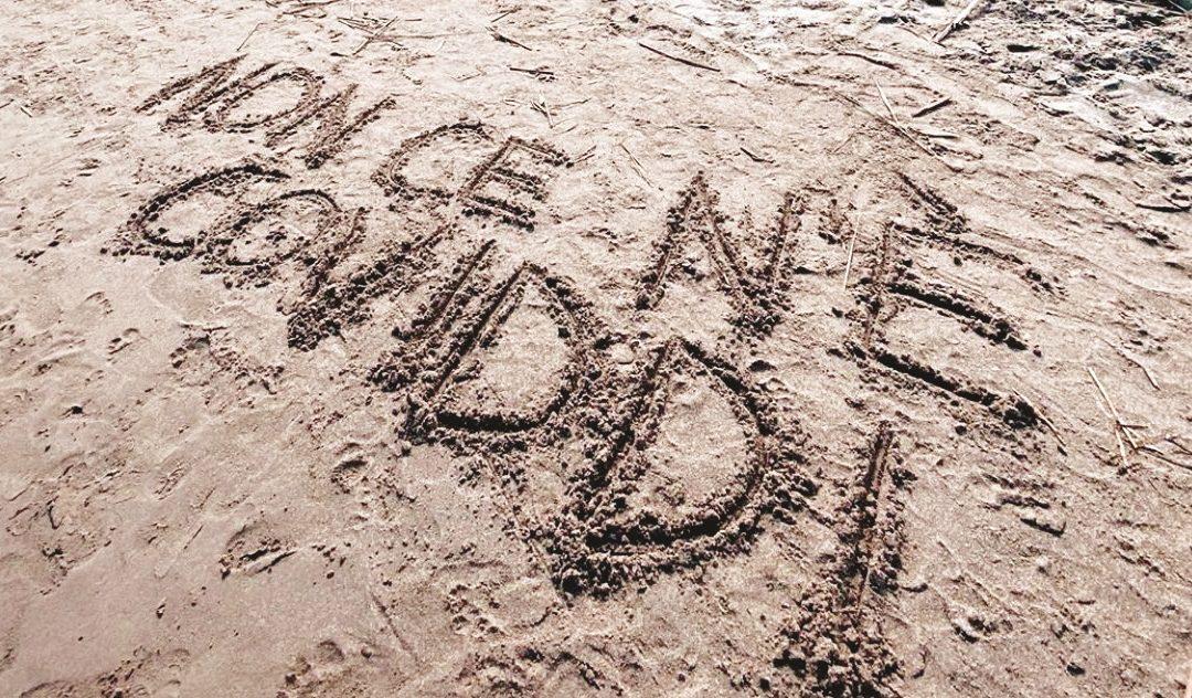 """Un'utente di Twitter posta la foto della frase tormentone di Angela Chianello """"Non ce n'è Coviddi"""", scritta sulla sabbia"""