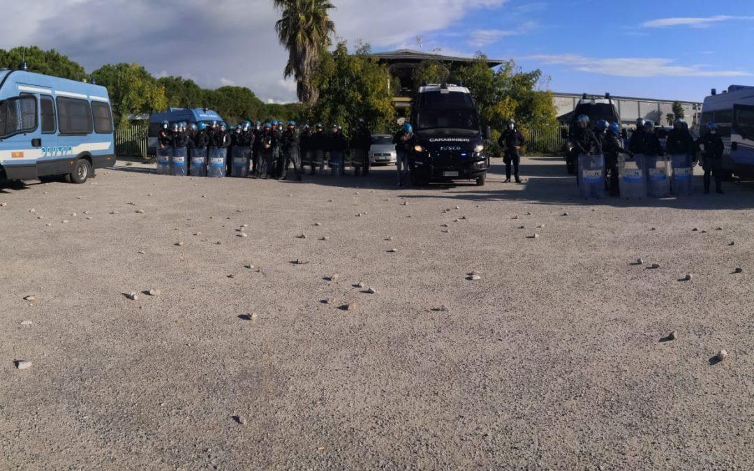 Forze dell'ordine schierate e i sassi lanciati dalla tendopoli