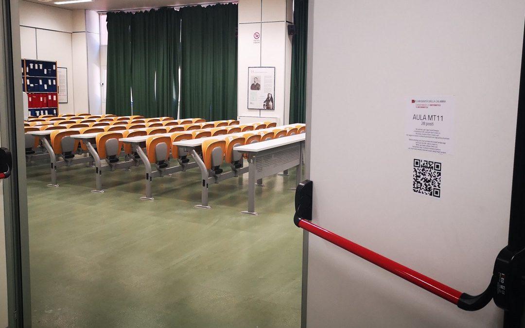 Un'aula dell'Unical con all'ingresso il QR code per il check-in