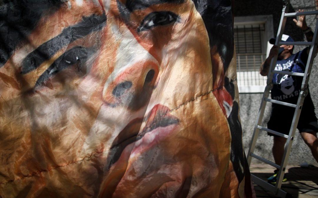 Tifosi appendono uno striscione dedicato Maradona all'esterno della clinica di La Plata