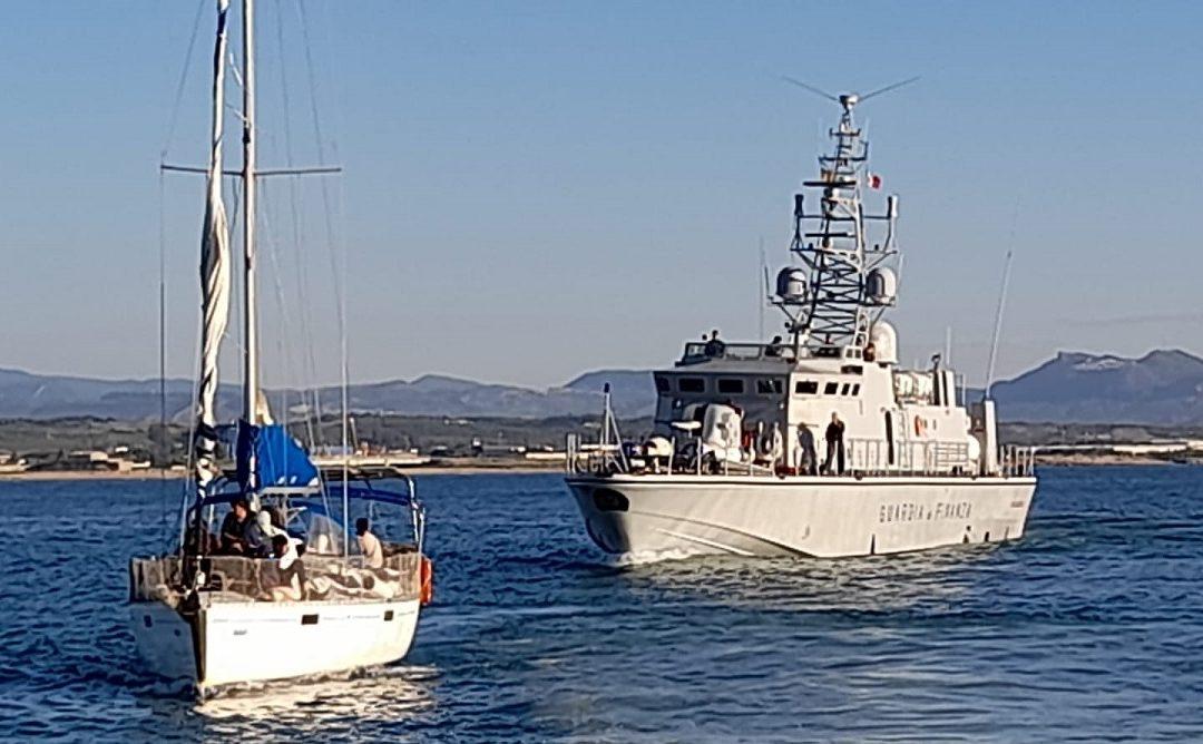 Una barca di migranti e la Guardia di finanza (foto d'archivio)